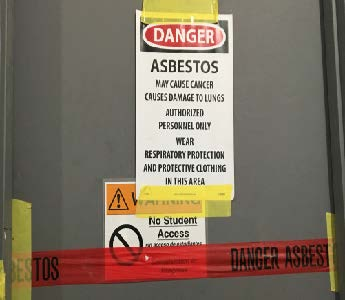 Signs on doors in S&E cautioning about asbestos and prohibiting student access. Photo by Alex Appel.