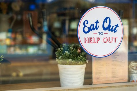 "An ""Eat Out to Help Out"" sticker on a restaurant window."